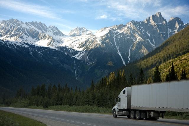 LKW fährt rRichtung Bergen unter einen blauen Himmel