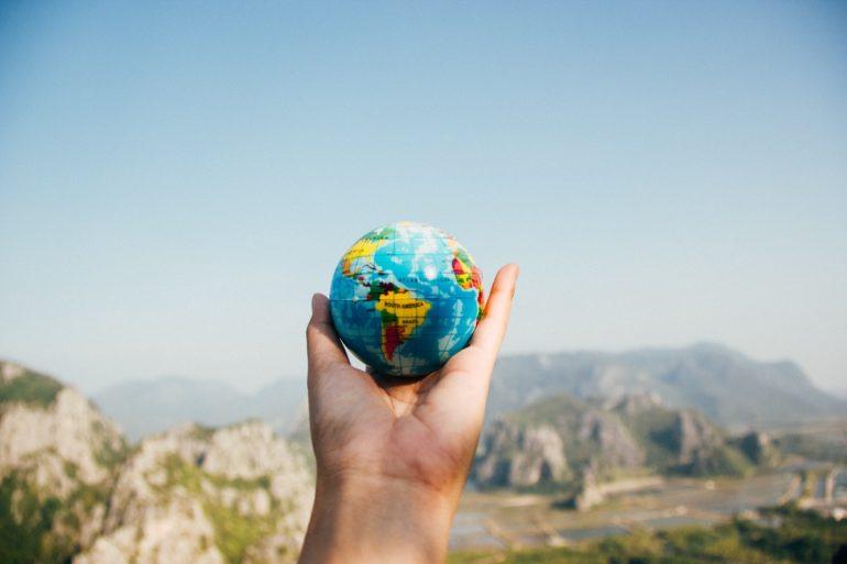 Hand hält die Welt mit blauem Himmel im Hintergrund